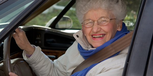 A senior woman at the wheel of her car
